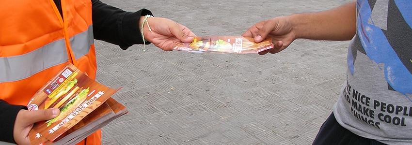 Persona entregándole un folleto a otra persona