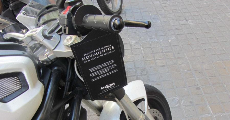 Motocicleta con publicidad colgada del manillar