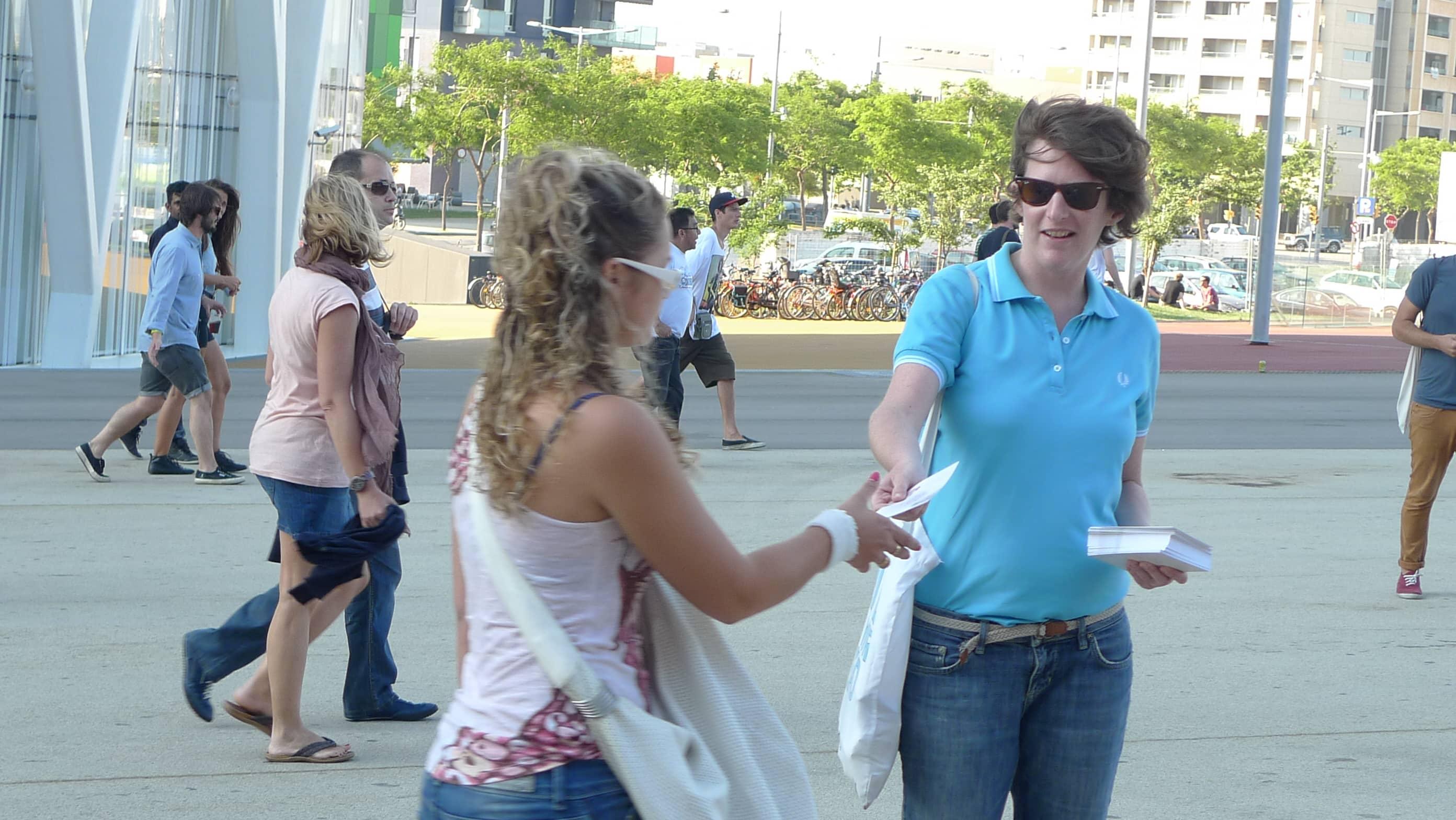 Persona repartiendo publicidad a personas en la calle